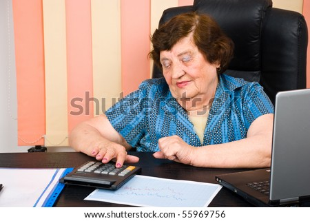 Senior business woman using calculator and sitting on chair in office