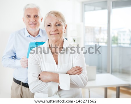 Senior businessman and a businesswoman  smiling and posing in their office. - stock photo