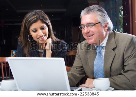 Senior businessman and young businesswoman looking at laptop computer - stock photo