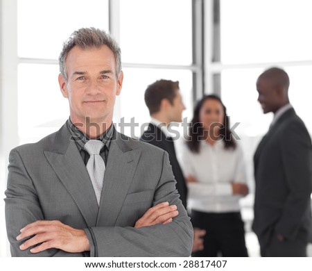 Senior Businessman being Positive with team in Background - stock photo