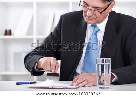 senior businessman concentrate on stamping document , approve contract - stock photo