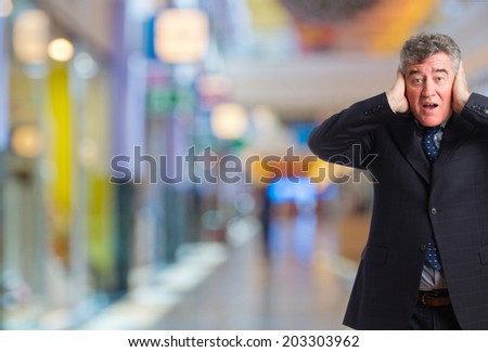 senior businessman covering his ears in a shopping center - stock photo