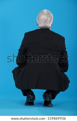 Senior businessman crouching with his back to the camera - stock photo