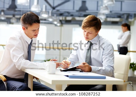 Senior businessman helping his younger colleague with financial analysis - stock photo