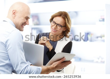 Senior businessman holding digital tablet and analyzing financial data while sitting with business woman at desk in front of computer. Teamwork at office.  - stock photo