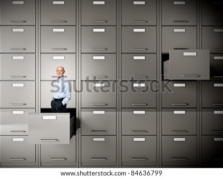 senior businessman in file cabinet drawer