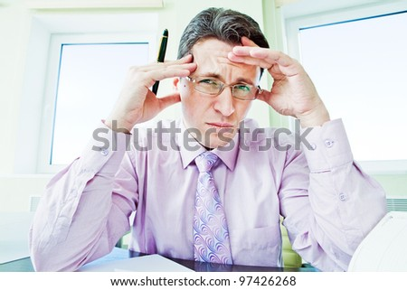 Senior businessman in stress working in office room