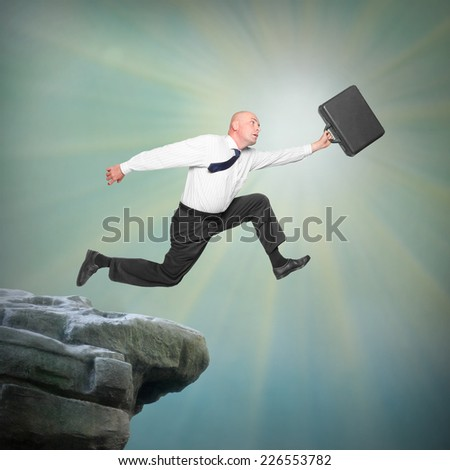 Senior businessman jumping from a edge of cliff. Career and insurance metaphor.  - stock photo