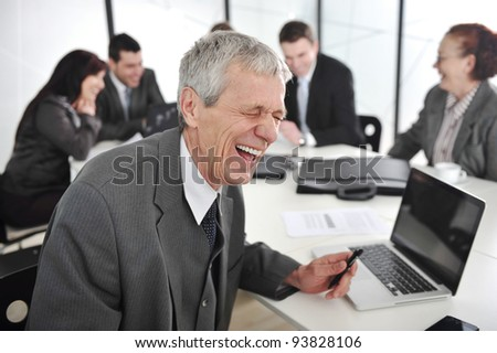 Senior businessman laughing at office meeting - stock photo
