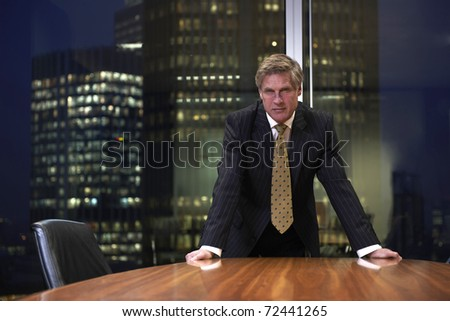Senior businessman leaning on boardroom table looking at camera