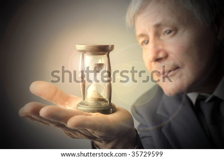 senior businessman looking at hourglass - stock photo
