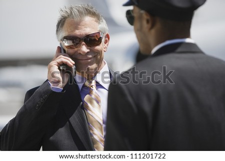 Senior businessman on a call while driver standing in the front at airfield - stock photo