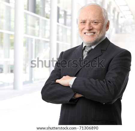 Senior businessman portrait, standing in office lobby with arms crossed, smiling at camera.? - stock photo