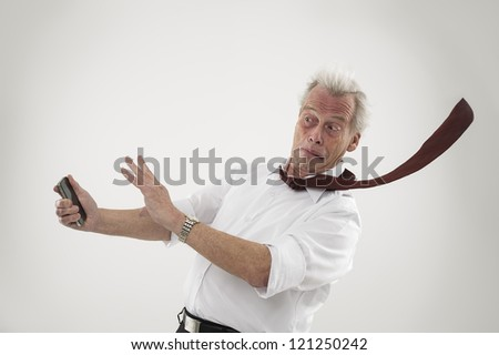 Senior businessman reacting in alarm as he is struck by high winds raising his hands into the defensive position, conceptual of a calamity or natural disaster affecting business - stock photo