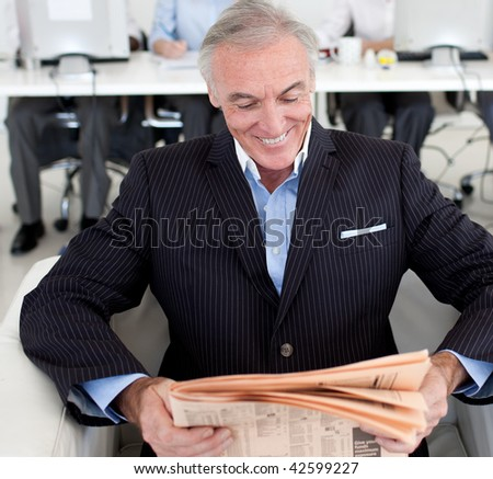 Senior businessman reading a newspaper with his team in the background