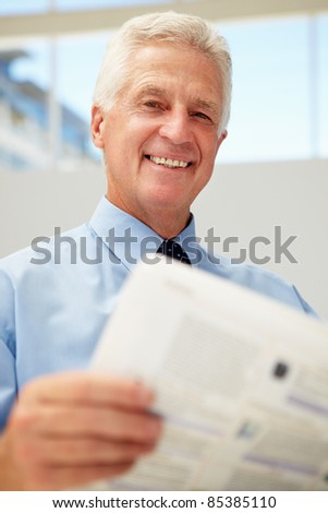 Senior businessman reading document - stock photo