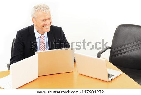 Senior businessman sitting in conference room and waiting for his colleagues - stock photo
