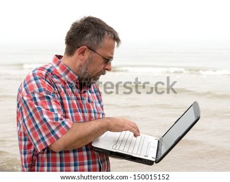 Senior businessman sitting with notebook on beach