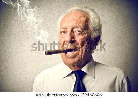 senior businessman smokes a cigar - stock photo