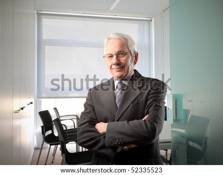 Senior businessman standing in a meeting room - stock photo