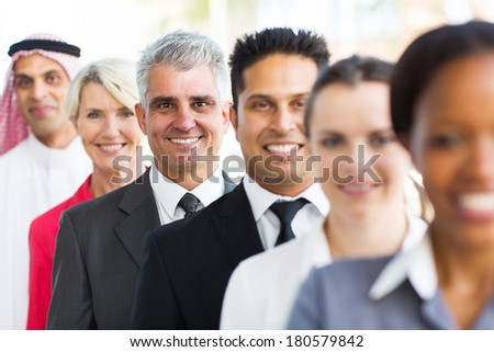 senior businessman standing in a row with colleagues - stock photo