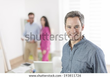 senior businessman standing in front of his colleagues in office - stock photo