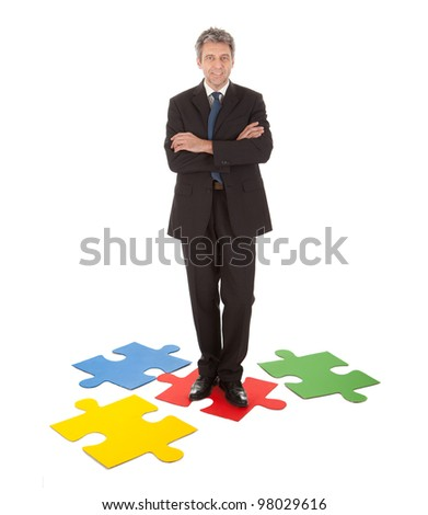 Senior businessman standing on a jigsaw puzzle. Isolated in white - stock photo