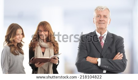 Senior businessman standing with colleagues at office. Teamwork.  - stock photo