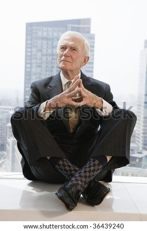 Senior businessman thinking with a city view - stock photo