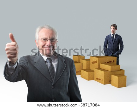 senior businessman thumb up and younger worker with 3d parcel - stock photo