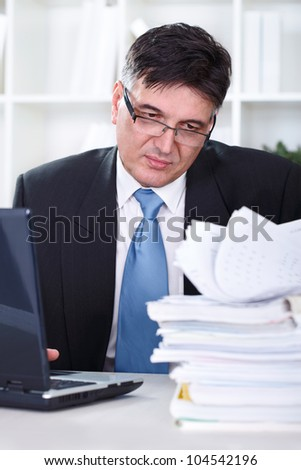 Senior businessman transferring data to the computer, working in office - stock photo
