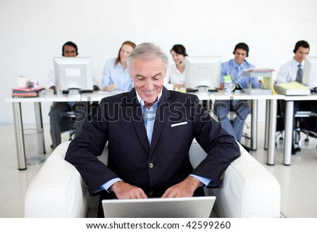 Senior businessman using a laptop with his team in the background - stock photo