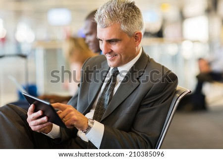 senior businessman using tablet computer while waiting for his flight at airport - stock photo