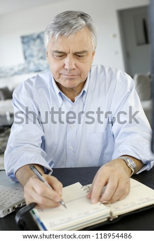 Senior businessman working from home - stock photo