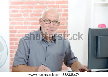 Senior businessman working on computer in his office - stock photo