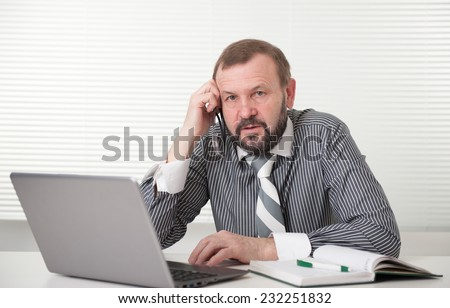 senior businessman working on his laptop in the office - stock photo