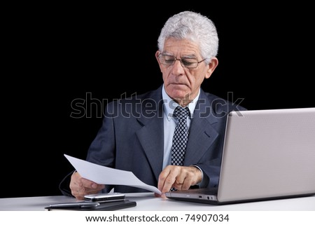 Senior businessman working on some documents at his office - stock photo