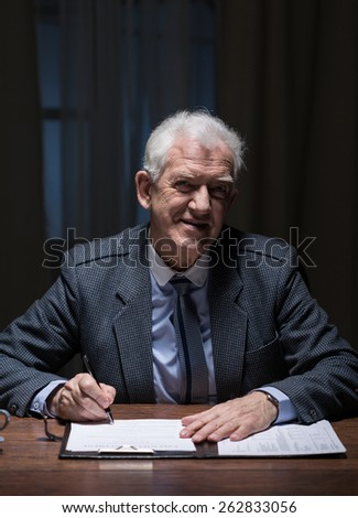 Senior businessman working overtime at the office - stock photo