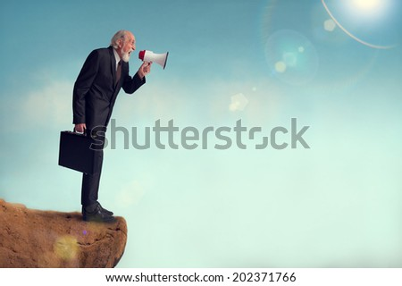 senior businessman yelling through a loudhailer from a cliff edge - stock photo