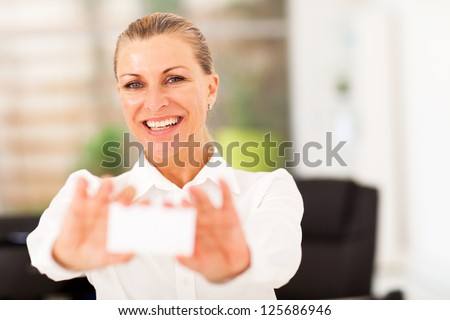 senior businesswoman holding business card - stock photo