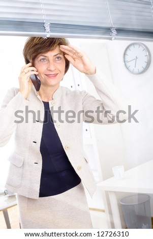 Senior businesswoman looking through the office window and calling on phone, smiling. - stock photo