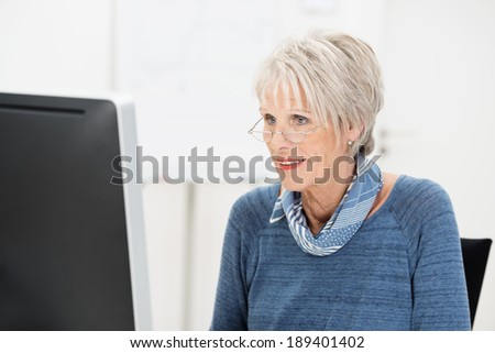 Senior businesswoman wearing glasses working at her desk reading the screen of her desktop computer monitor - stock photo