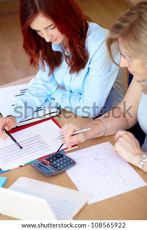 Senior businesswoman with junior colleague works on some paperwork - stock photo