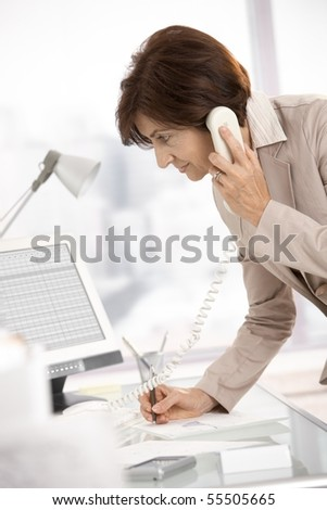 Senior businesswoman working in office, standing at desk, talking on landline phone, taking notes. - stock photo
