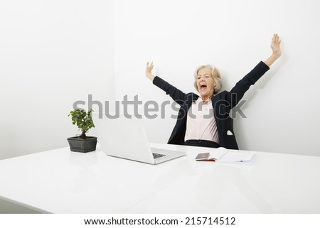 Senior businesswoman yawning while looking at laptop in office - stock photo