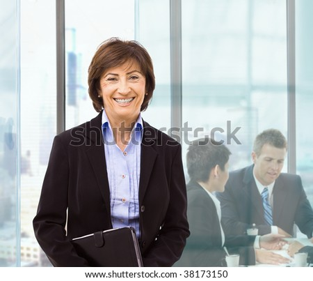 Senior businesswomanstanding in office holding personal organizer. Businesspeople working at desk in background. - stock photo