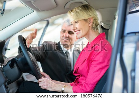 senior car sales consultant showing a new car to mature female customer - stock photo
