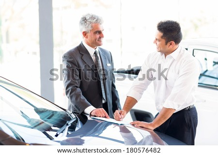 senior car salesman just made a sale to young customer - stock photo