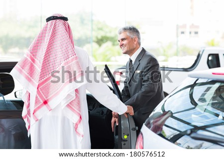 senior car salesman showing a new car to Arabian man - stock photo