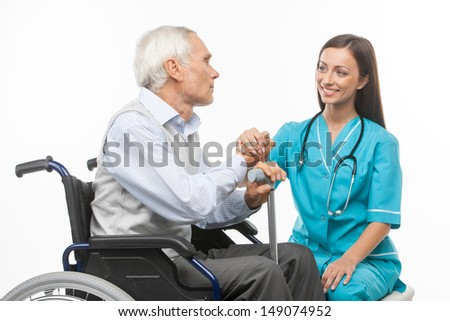 Senior care. Cheerful young nurse holding senior man hand and smiling while isolated on white - stock photo